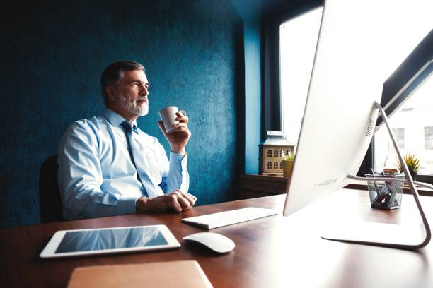 Focused mature businessman deep in thought while sitting at a table in modern office. Focused mature businessman deep in thought while sitting at a table in modern office ceo stock pictures, royalty-free photos & images