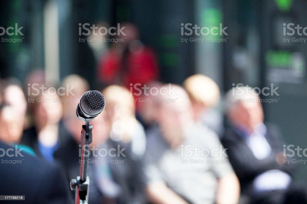 A focused microphone close up with a blurry audience  stock photo