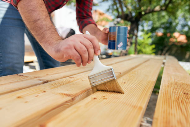 Focused mid adult carpenter varnish a wooden board with protective oil stock photo