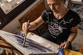 istock Focused mid adult female painter defining her painting on canvas with acrylic colors 1254538941