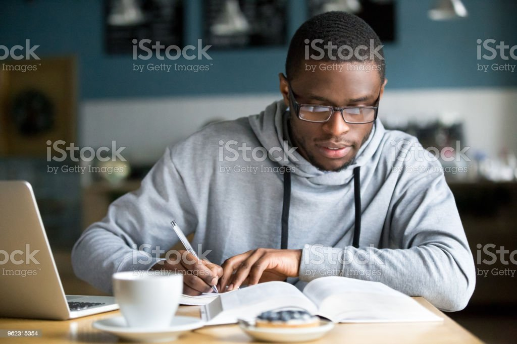 Focused millennial african student making notes while studying in cafe royalty-free stock photo