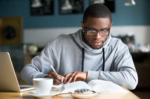 istock Focused millennial african student making notes while studying in cafe 962315354