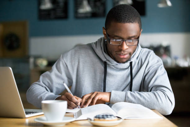 Focused millennial african student making notes while studying in cafe stock photo