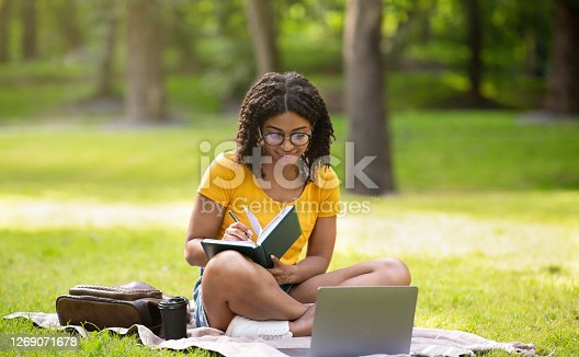 istock Focused millennial black girl writing something in notebook near laptop computer at park 1269071678