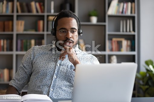 1031235468 istock photo Focused millennial mixed race guy consulting clients online. 1216968885