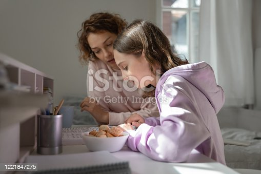 1051247474 istock photo Focused mom helping teenage daughter doing homework studying from home 1221847275