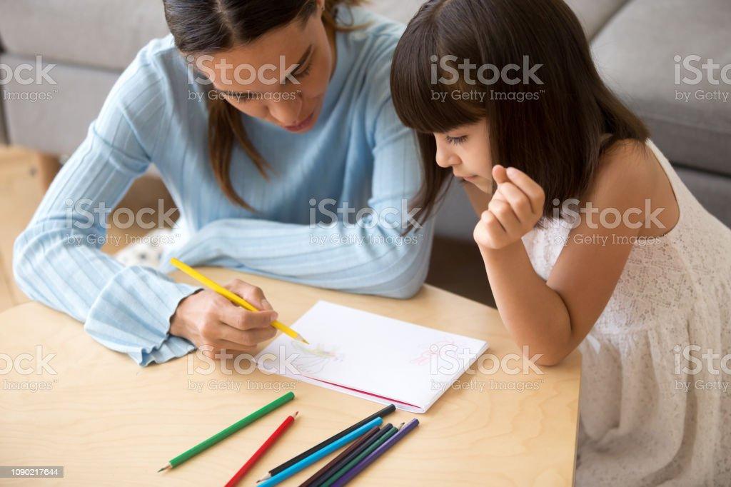 Focused Mom Holding Colored Pencil Teaching Kid Daughter To Draw Fotografie Stock E Altre Immagini Di Accudire Istock