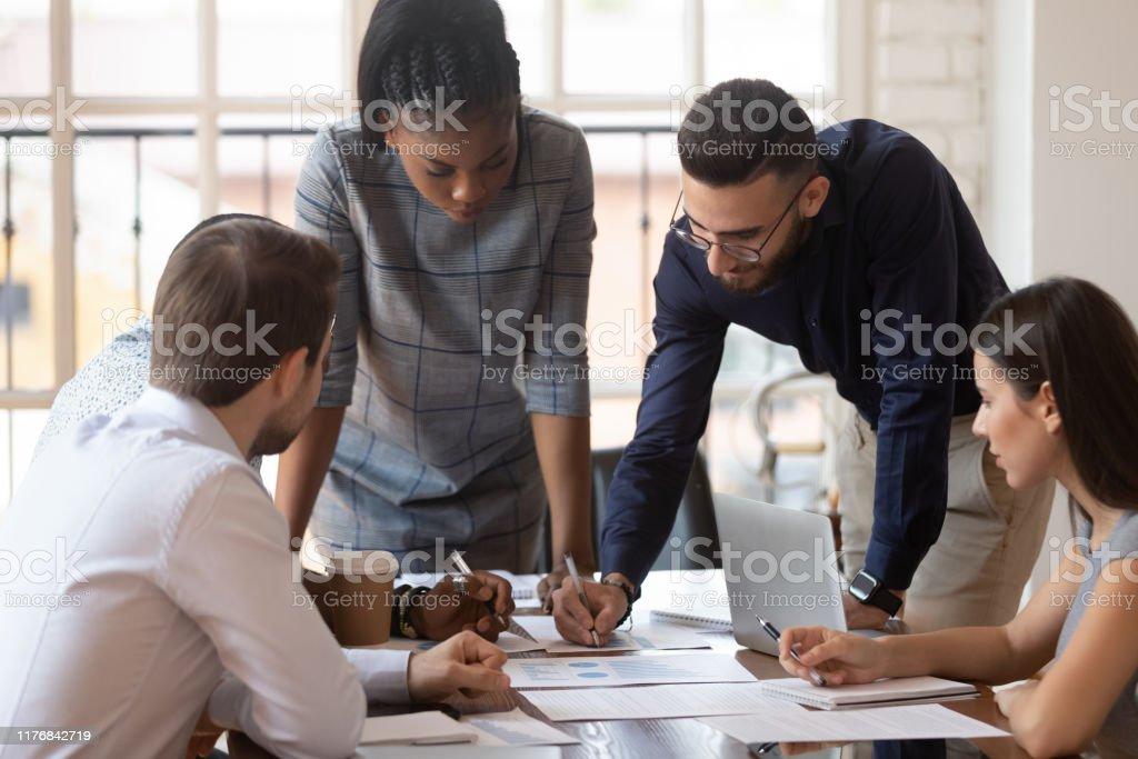 Focused multiracial corporate business team people brainstorm on paperwork - Стоковые фото Анализировать роялти-фри