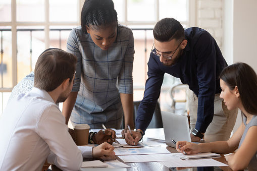 Focused Multiracial Corporate Business Team People Brainstorm On Paperwork Stock Photo - Download Image Now