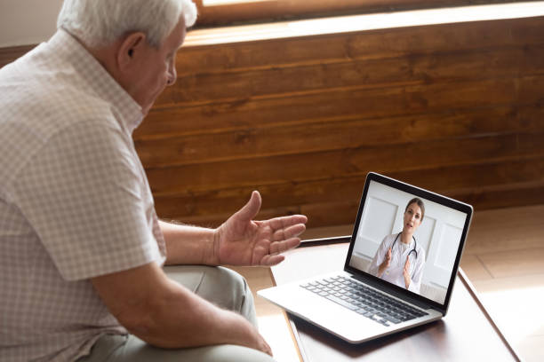 Focused older 80s patient consulting with doctor via video call. Focused older 80s male patient consulting with doctor via computer video call. Senior man looking at laptop screen, talking to therapist cardiologist online, older generation using modern technology. bingo caller stock pictures, royalty-free photos & images