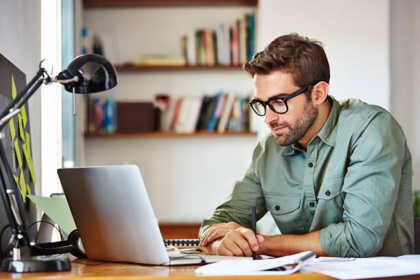 focused on his work - sitting laptop стоковые фото и изображения