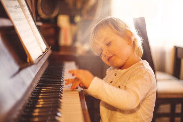 Focused on playing perfectly. Focused on playing perfectly. Little boy playing piano. child prodigy stock pictures, royalty-free photos & images