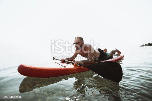 Focused Paddleboarder Traversing Lake During Summer Vacation