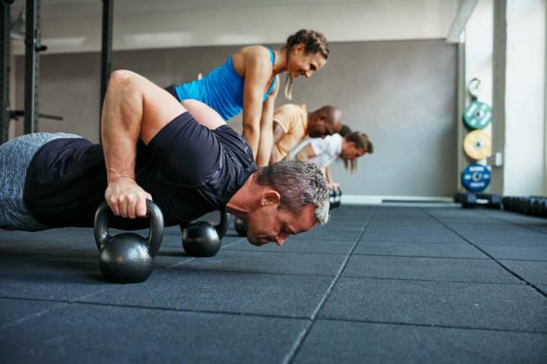 Enfocado a gente que hace flexiones en pesos en una clase de gimnasia - foto de stock