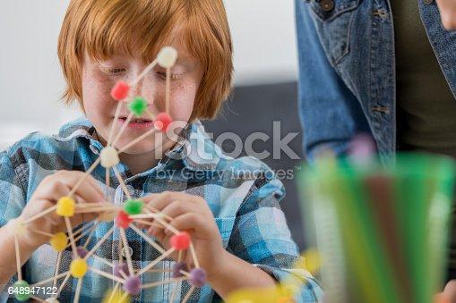 648947070 istock photo Focused schoolboy makes something in engineering club 648947122