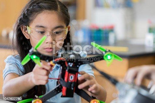 istock Focused schoolgirl builds quadcopter 1042602780