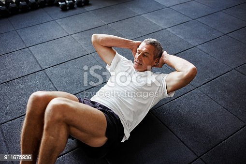 istock Focused senior man doing an ab workout in a gym 911675936