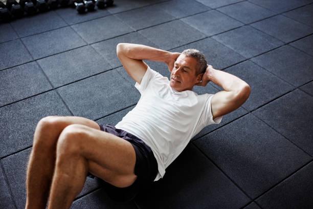 focused senior man doing an ab workout in a gym - sit ups stock photos and pictures