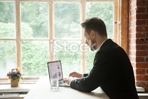 istock Focused serious businessman working on laptop analyzing project statistics data 912234892