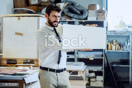 848290020 istock photo Focused serious caucasian bearded supervisor in suit and tie looking at proof while standing in printing shop. 1187323291