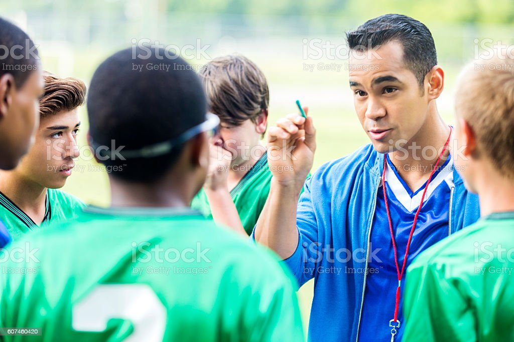 Focused soccer coach gives players a pep talk stock photo