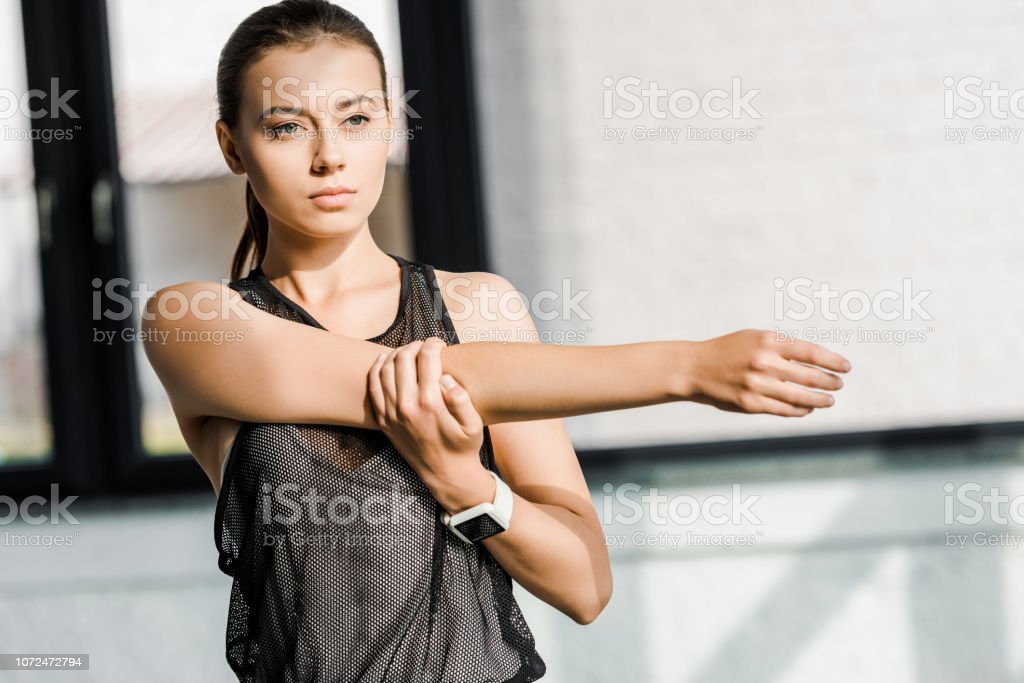 focused sportswoman doing stretching exercise before training session at fitness studio