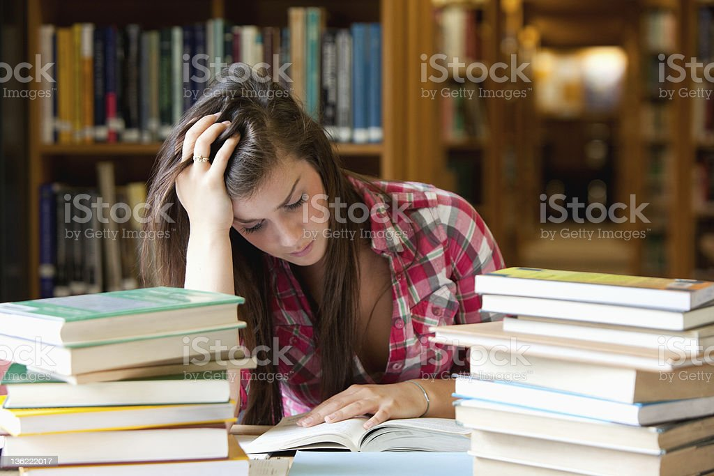 Focused student surrounded by books royalty-free stock photo