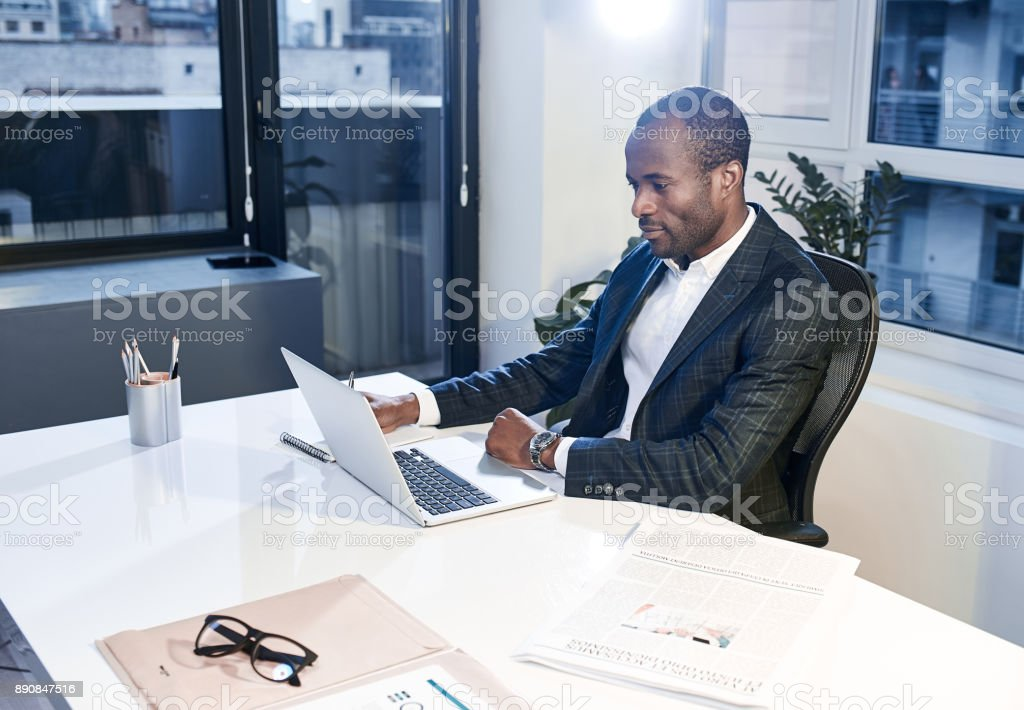 Focused stylish businessman is looking at monitor of his gadget stock photo