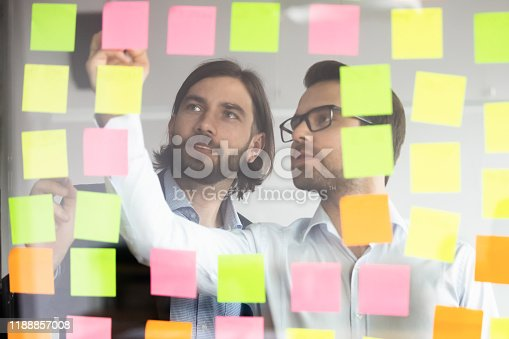 1144568493 istock photo Focused successful teammates working together near kanban board. 1188857008