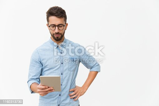 Focused tablet user reading content on screen. Handsome young man in casual shirt and glasses standing isolated over white background. Wireless internet technology concept