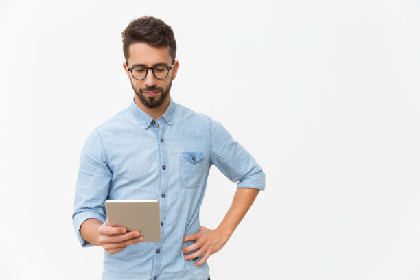 Focused tablet user reading content on screen stock photo