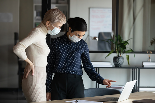 Focused two young multiracial business women in medical facial protective masks standing near table, looking at laptop screen, discussing project details, preventing spreading corona virus in office.