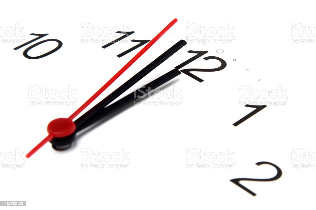 focused view of analog clock with all hands close to 12:00 stock photo
