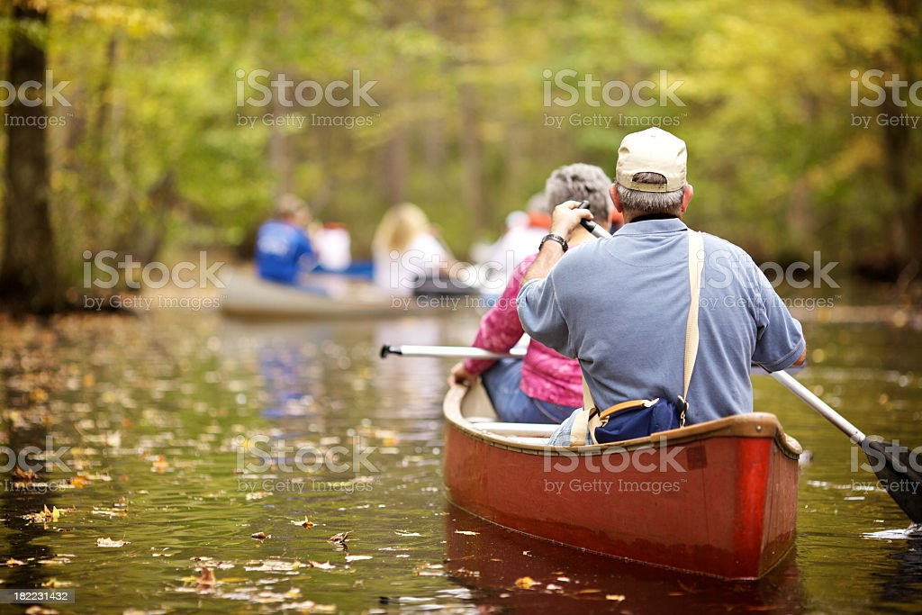 Focused view of senior pair paddling a canoe stock photo