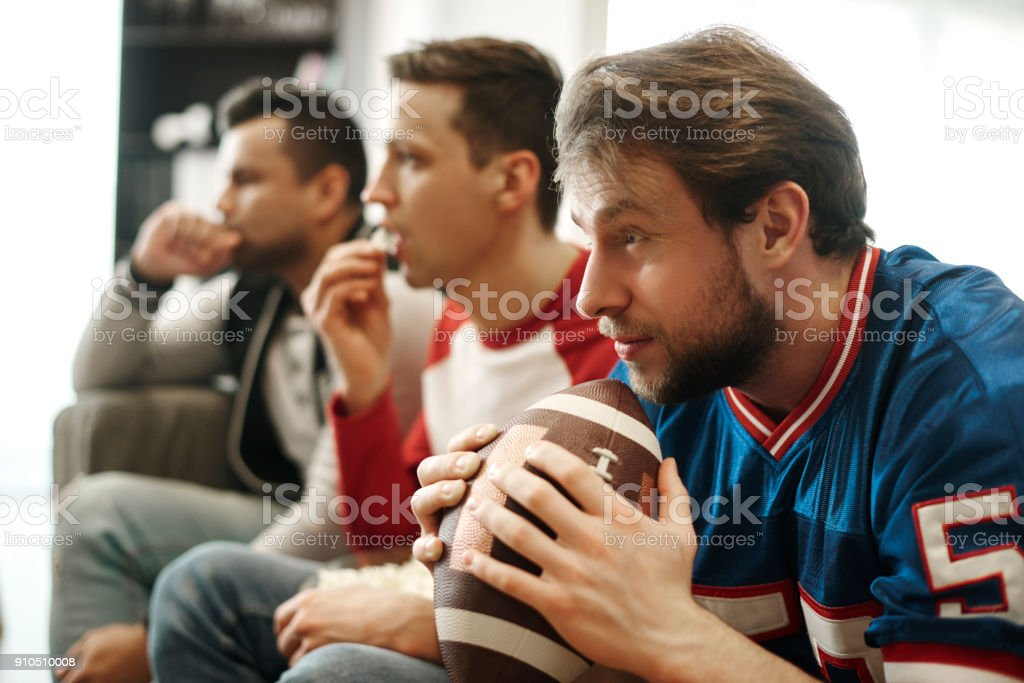 Focused watching football game at home stock photo