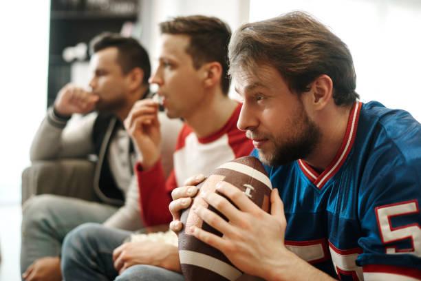 enfocado viendo partido de fútbol en casa - american football fotografías e imágenes de stock
