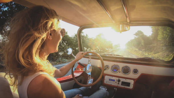 Focused woman in sunglasses with blond hair drives a car without a roof stock photo