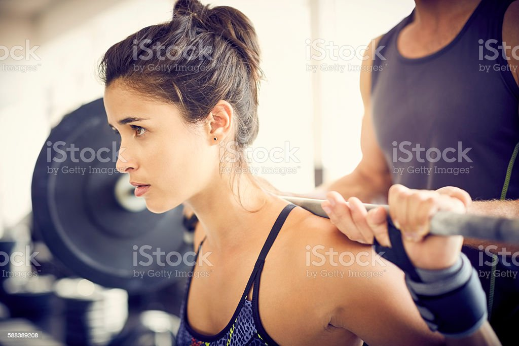 Focused woman lifting barbell while coach assisting her in gym stock photo