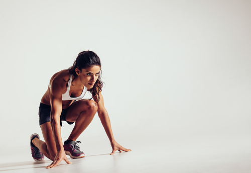 Female athlete in position ready to run over grey background. Determined young woman ready for a sprint.