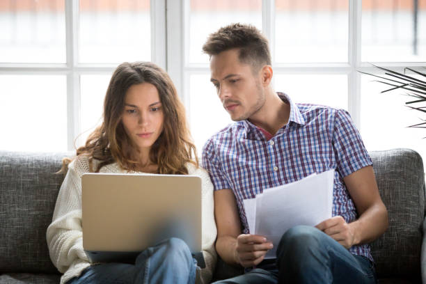 focused worried couple paying bills online on laptop with documents - bills couple imagens e fotografias de stock