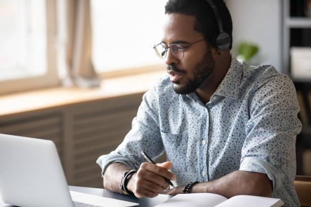 Joven afroamericano enfocado viendo una conferencia educativa en línea. - foto de stock