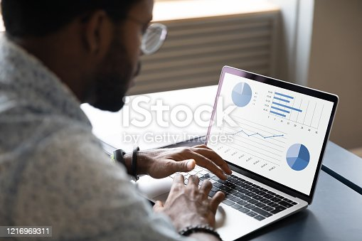 Focused young african ethnicity male marketing specialist professional working on project report, analyzing graphs charts in economic application on computer, sitting at table in office or home.