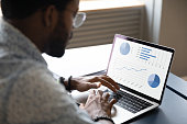 istock Focused young african ethnicity male marketing specialist analyzing graphs. 1216969311