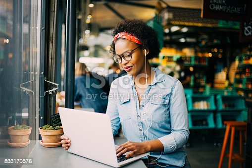 Focused young African woman sitting alone at a counter in a cafe working on a laptop and listening to music on earphones