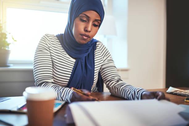 konzentrierte sich arabische jungunternehmer in ihrem büro zu hause arbeiten - lesen arbeitsblätter stock-fotos und bilder