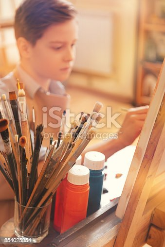 123499844istockphoto Focused young artist painting on art canvas in studio 854025354