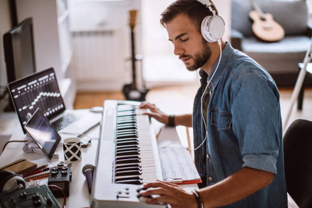 Focused Young Artist Playing Electric Piano Inspired Young Artist Playing Electric Piano In His Comfortable Home hobbies stock pictures, royalty-free photos & images
