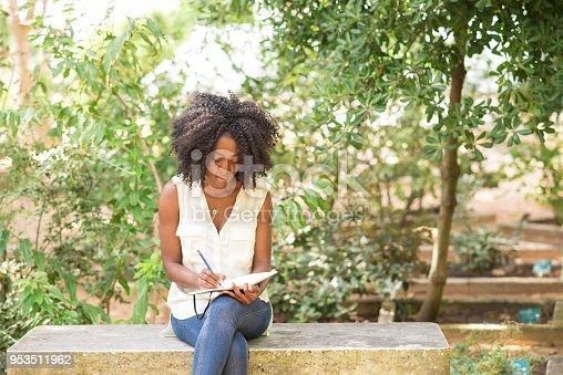istock Focused young attractive black woman making notes in park 953511962