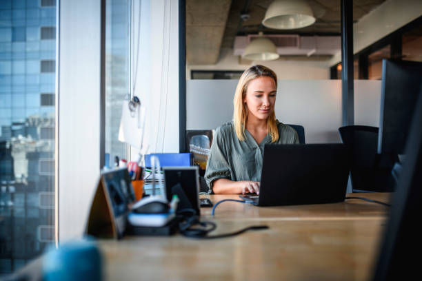 Focused Young Businesswoman Working on Laptop in Office stock photo