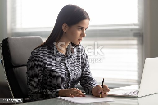 958531418 istock photo Focused young confident businesswoman working with paper documents. 1182227873